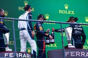 George Russell, Williams, 2nd position, Max Verstappen, Red Bull Racing, 1st position, and Lewis Hamilton, Mercedes, 3rd position, celebrate with Champagne on the podium