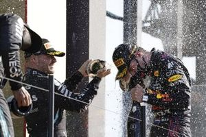 Lewis Hamilton, Mercedes, 2nd position, and Valtteri Bottas, Mercedes, 3rd position, spray Champagne at Max Verstappen, Red Bull Racing, 1st position, on the podium