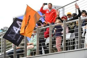 Young fans wave flags from a grandstand