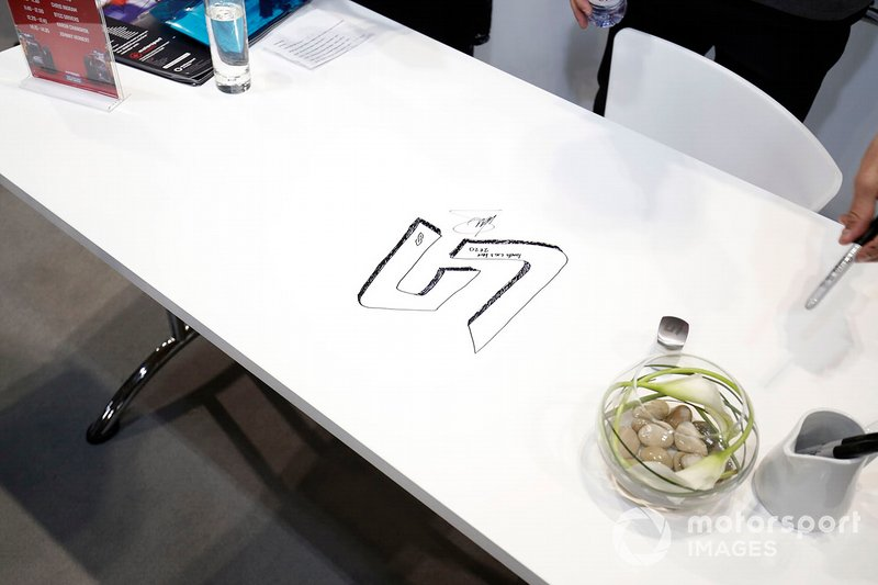 Lando Norris leaves his mark on a table at the Autosport show