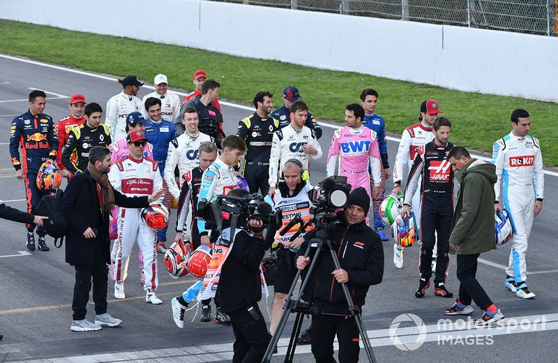 The drivers are directed into position for a group photograph