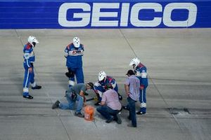 Workers patch a hole in the race track