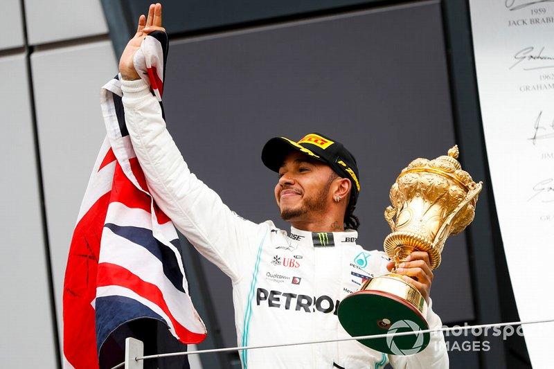 Il vincitore della gara Lewis Hamilton, Mercedes AMG F1, sul podio con il trofeo e una bandiera