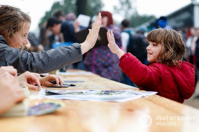 Caitlin Wood con un joven fan en la sesión de autógrafos de las pilotos