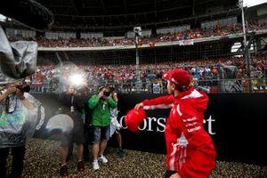 Sebastian Vettel, Ferrari, throws a cap into the crowd