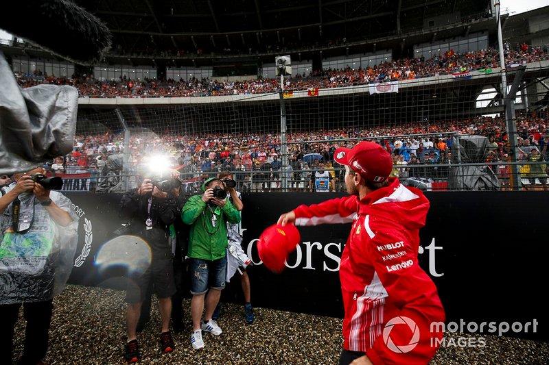 Sebastian Vettel, Ferrari, lanza una gorra a la multitud