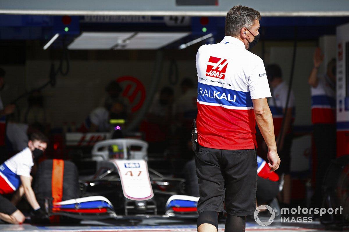 Un mecánico se pone en posición para dirigir a Mick Schumacher, Haas VF-21, fuera del garaje