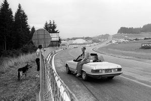 Denny Hulme, former McLaren driver, sits on a Mercedes car out on the circuit with Phil Kerr, McLaren Racing Director