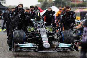 Mechanics push the car of Lewis Hamilton, Mercedes W12, on the grid