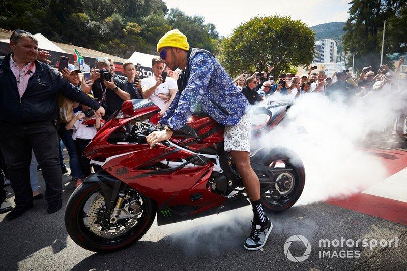 Lewis Hamilton, Mercedes AMG F1, arriva a bordo di una moto, facendo fumare le gomme