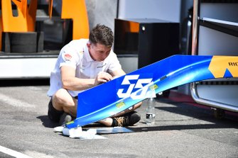 McLaren mechanic adding racing number decal on engine cover