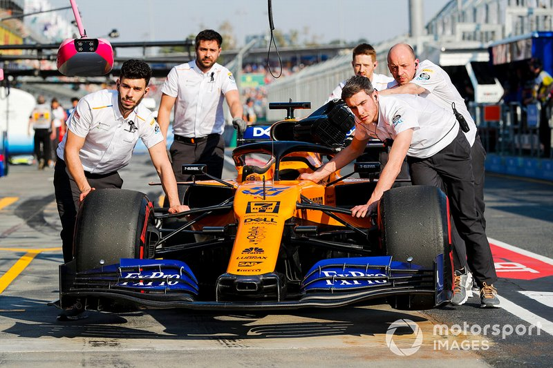 Mecánicos mueven el coche de Carlos Sainz Jr., McLaren MCL34
