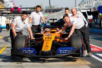 McLaren mechanics move the car of Carlos Sainz Jr., McLaren MCL34