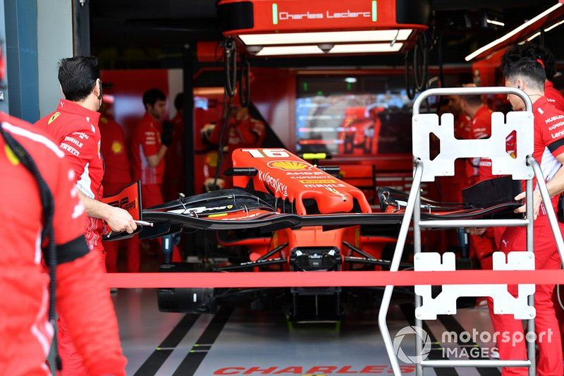 Mechanics move a front wing for the Ferrari SF90