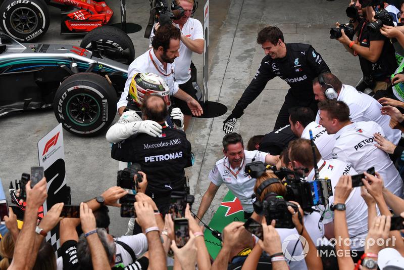 Las barreras se derrumban cuando Lewis Hamilton, Mercedes AMG F1 celebra con su mecánica en el Parc Ferme.