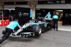 Wagen van Lewis Hamilton, Mercedes AMG F1 W09 EQ Power+ wordt door monteurs naar de pitbox geduwd