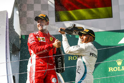 Sebastian Vettel, Ferrari, 2nd position, and Lewis Hamilton, Mercedes AMG F1, 1st position, spray Champagne on the podium