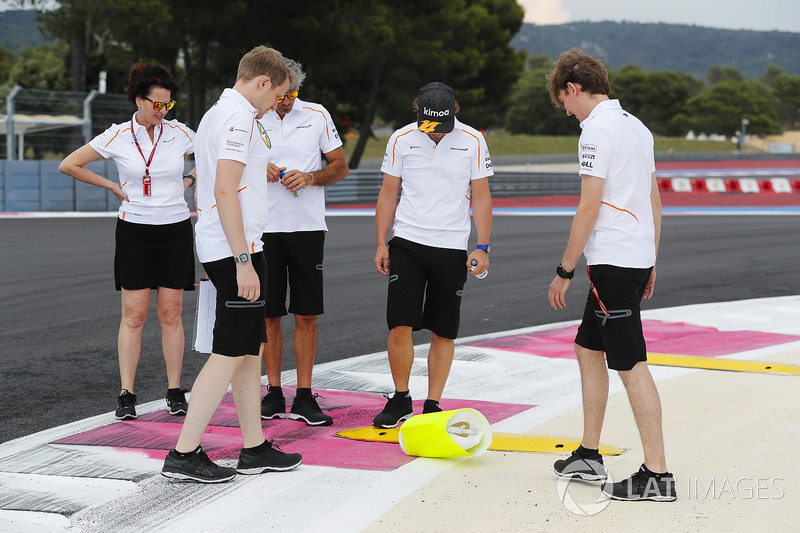 Fernando Alonso, McLaren, inspects a kerb with colleagues