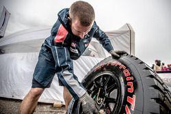Peugeot Sport team member checks a tire