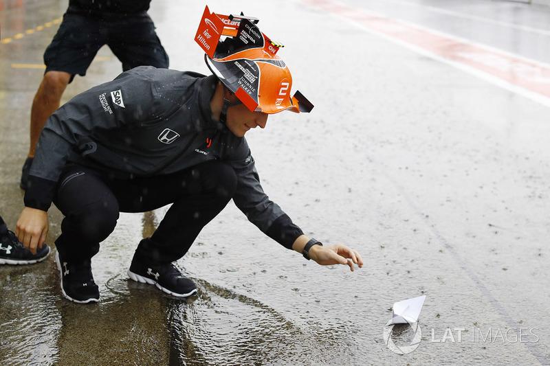 Stoffel Vandoorne, McLaren, pone un barco de papel en la corriente de agua en el pit lane