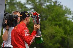 El ganador de la carrera, Sebastian Vettel, Ferrari celebra en el podio con el trofeo