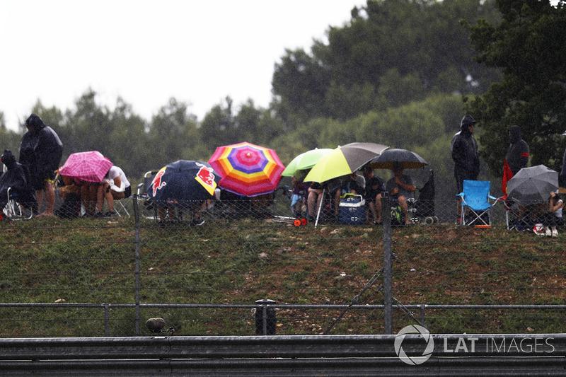 Los espectadores se resguardan de la lluvia bajo los paraguas