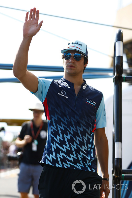 Lance Stroll, Williams Racing, waves while walking in the pit lane