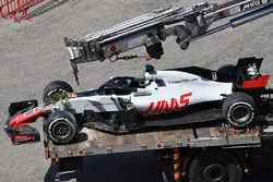 The crashed car of Romain Grosjean, Haas F1 Team VF-18 is recovered to the pits in FP2