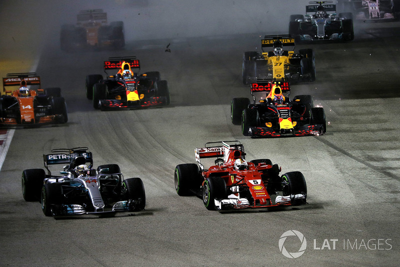 Sebastian Vettel, Ferrari SF70H leads at the start of the race, a damaged radiator ahead of the damaged car of Max Verstappen, Red Bull Racing RB13 after crashing and colliding, Kimi Raikkonen, Ferrari SF70H