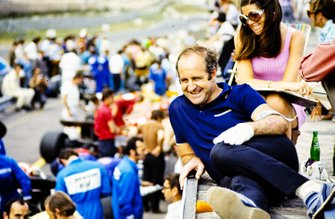 Denny Hulme relaxing above the pit lane