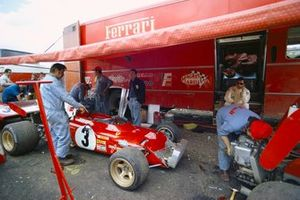 Jacky Ickx watches the mechanics work on his Ferrari 312B2