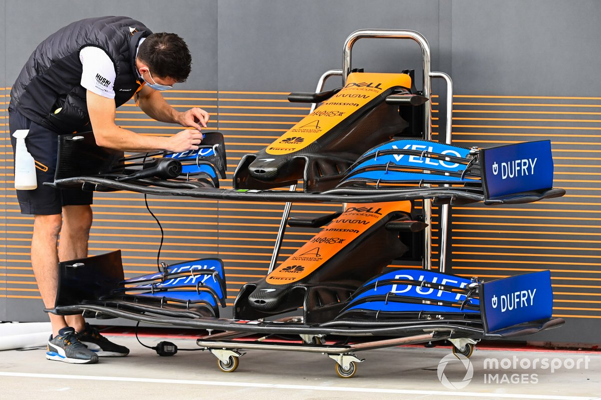 A McLaren mechanic at work on a front wing endplate