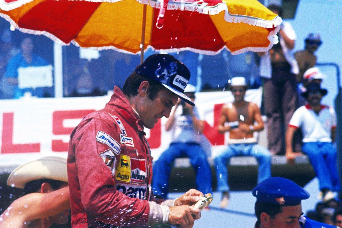 Carlos Reutemann, Ferrari celebra su victoria en el podio intentando abrir su botella de champán