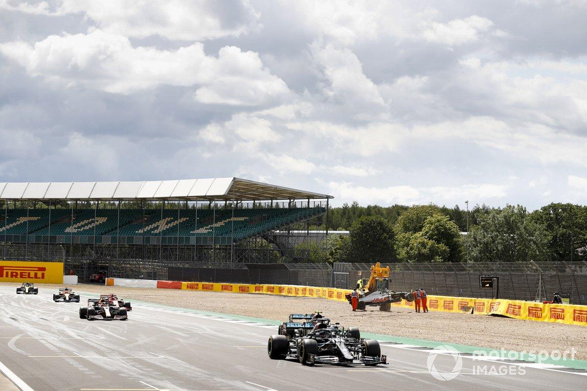 Lewis Hamilton, Mercedes F1 W11, Valtteri Bottas, Mercedes F1 W11, e Max Verstappen, Red Bull Racing RB16,passano l'auto incidentata di Magnussen, Haas VF-20