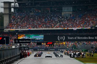 The Safety Car leads Lewis Hamilton, Mercedes AMG F1 W10, Max Verstappen, Red Bull Racing RB15, and the rest of the field away