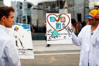 Lando Norris, McLaren and Carlos Sainz Jr., McLaren paint for a TV feature