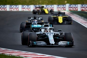Lewis Hamilton, Mercedes AMG F1 W10, leads Romain Grosjean, Haas F1 Team Team VF-19, and Daniel Ricciardo, Renault F1 Team R.S.19