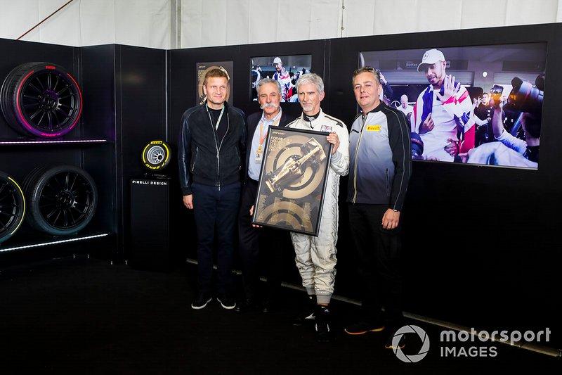 Chase Carey, presidente de Fórmula 1, Damon Hill y Mario Isola, gerente de carreras de Pirelli Motorsport, presentan el póster oficial de la carrera 1000 de F1