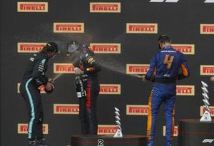 Lewis Hamilton, Mercedes, 2nd position, Max Verstappen, Red Bull Racing, 1st position, and Lando Norris, McLaren, 3rd position, celebrate with Champagne on the podium