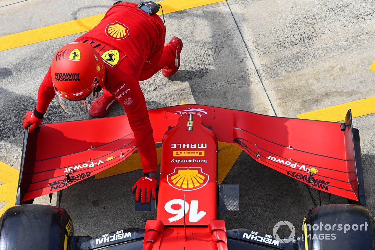 Un meccanico della Ferrari, mentre spinge l' auto di Charles Leclerc, Ferrari SF21 dentro il garage