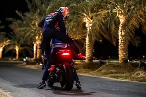 Max Verstappen, Red Bull Racing, gets on a course motorcycle after retiring