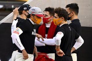 Carlos Sainz Jr., McLaren, talks with Lando Norris, McLaren, on the grid