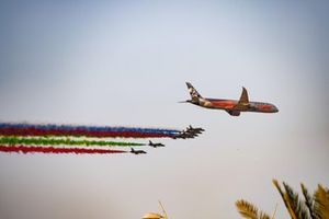 The United Arab Emirates Air Force display team Al Fursan escort an Etihad Boeing 787 Dreamliner in the ir Aermacchi MB-339NAT jet trainers over the grid, prior to the start