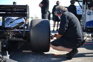 A crew member checks tyre pressure