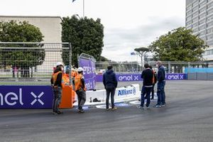 Marshals and FIA members inspect the damaged kerb