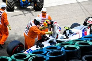 Marshals assist Mick Schumacher, Haas VF-21, after his crash in FP3
