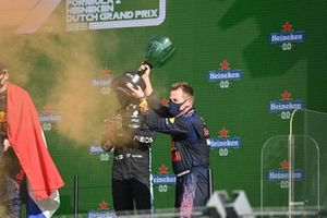 The Red Bull trophy delegate lifts the constructors trophy on the podium
