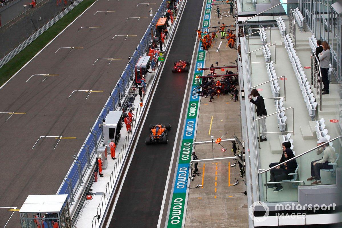 Max Verstappen, Red Bull Racing RB16B, en boxes mientras Carlos Sainz Jr., Ferrari SF21, y Daniel Ricciardo, McLaren MCL35M, pasan