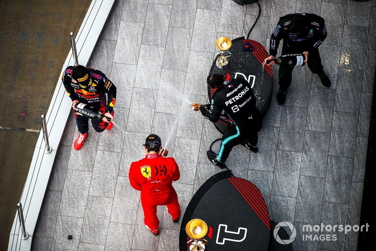 Max Verstappen, Red Bull Racing, 2a posizione, Carlos Sainz Jr, Ferrari, 3a posizione, Lewis Hamilton, Mercedes, 1a posizione, e il rappresentante del team Mercedes spruzza Champagne sul podio