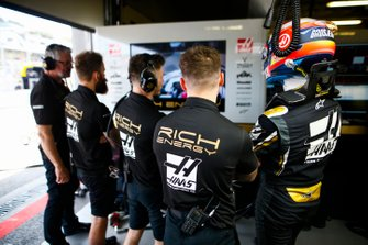 Romain Grosjean, Haas F1, with team mates in the garage
